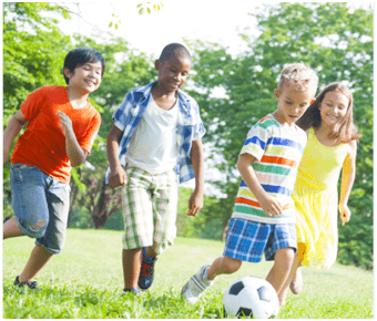 Children kicking a soccer ball outside in physical education