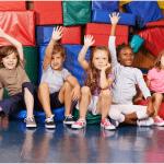 Kids sitting on floor with hands raised